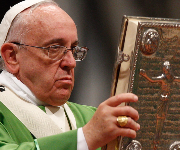 Pope Francis raises the Book of the Gospels as he celebrates a Mass to open the extraordinary Synod of Bishops on the family in St. Peter's Basilica at the Vatican Oct. 5. (CNS/Paul Haring)